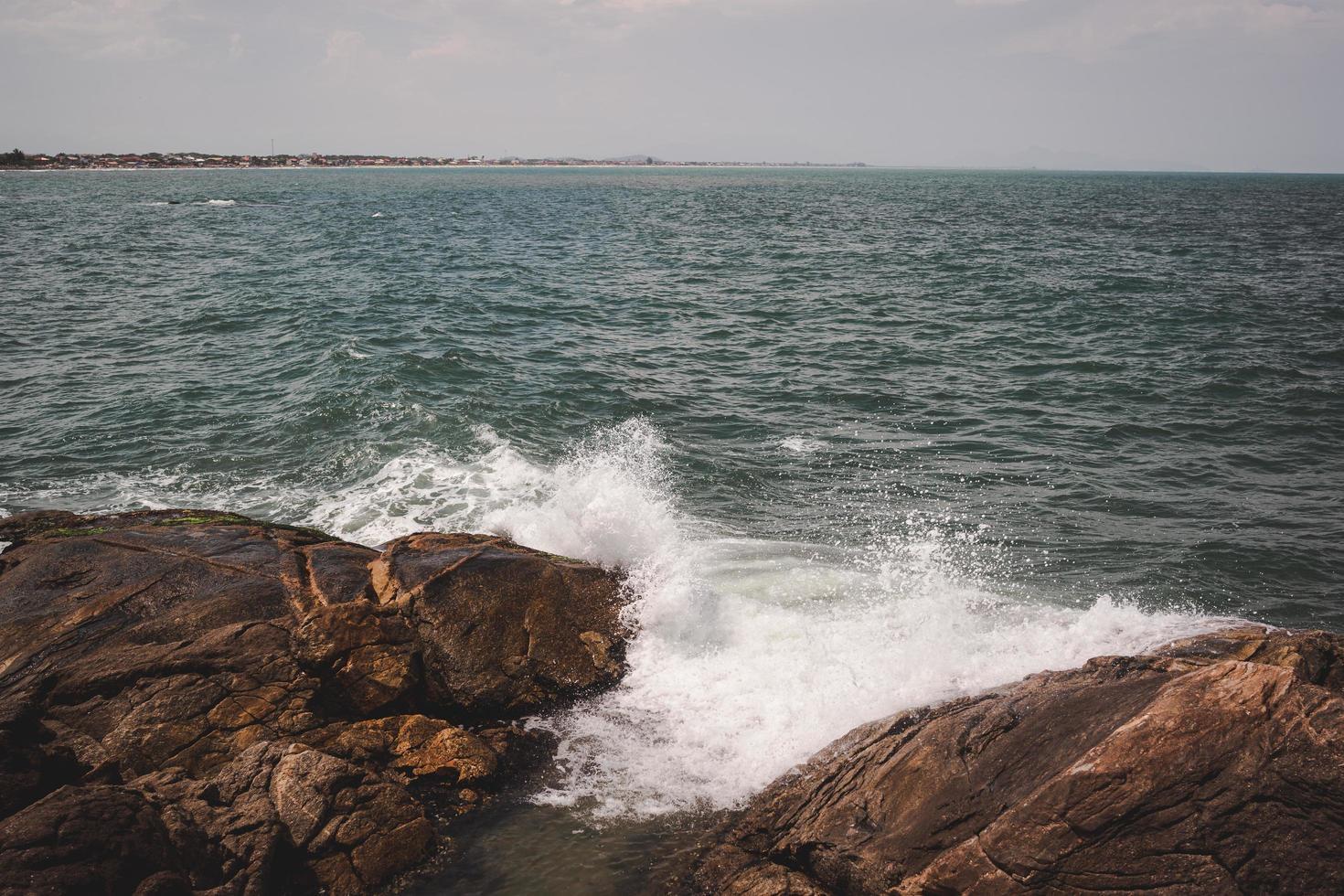 vågor kraschar på stenar foto