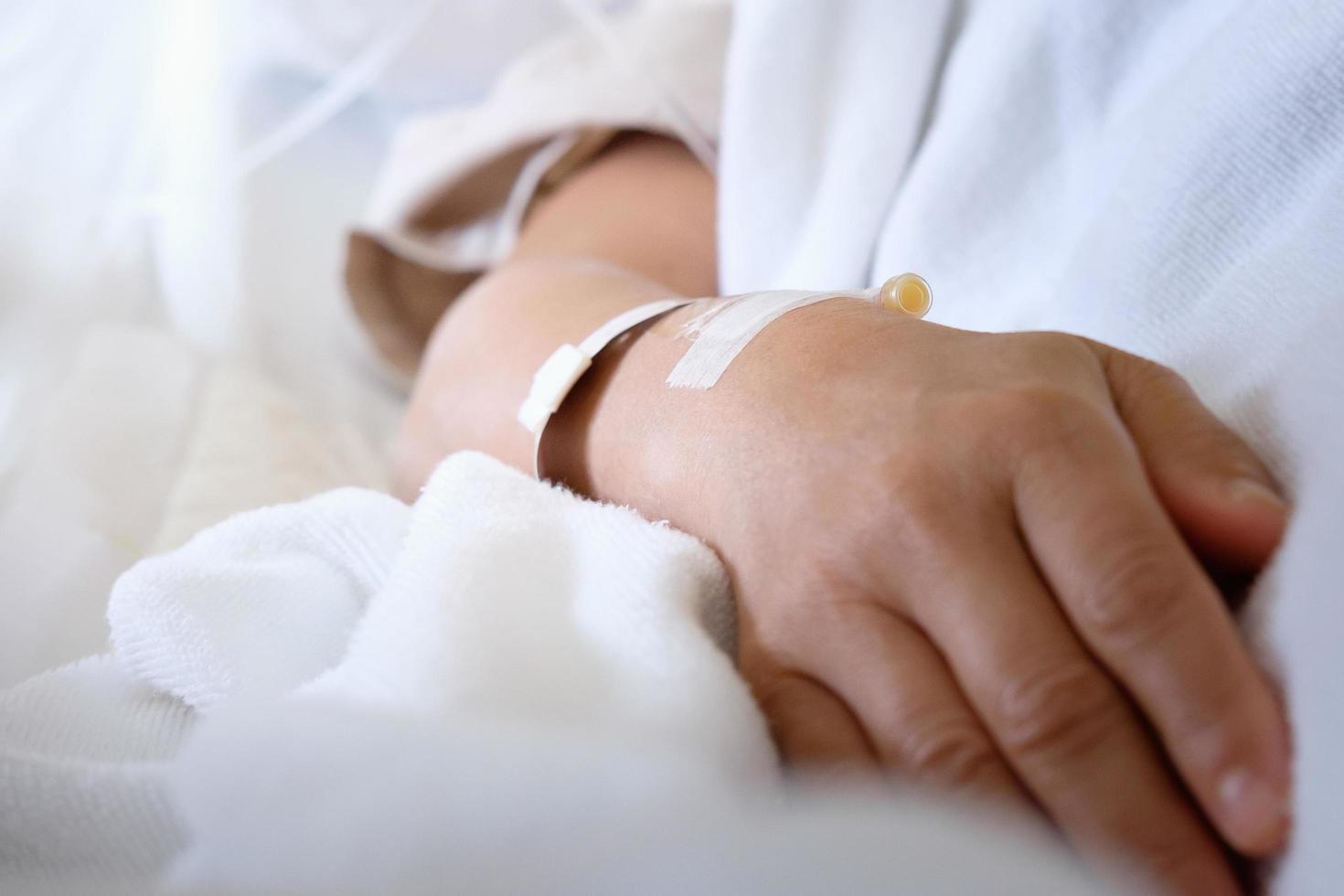 närbild av intravenöst rör på patientens hand foto