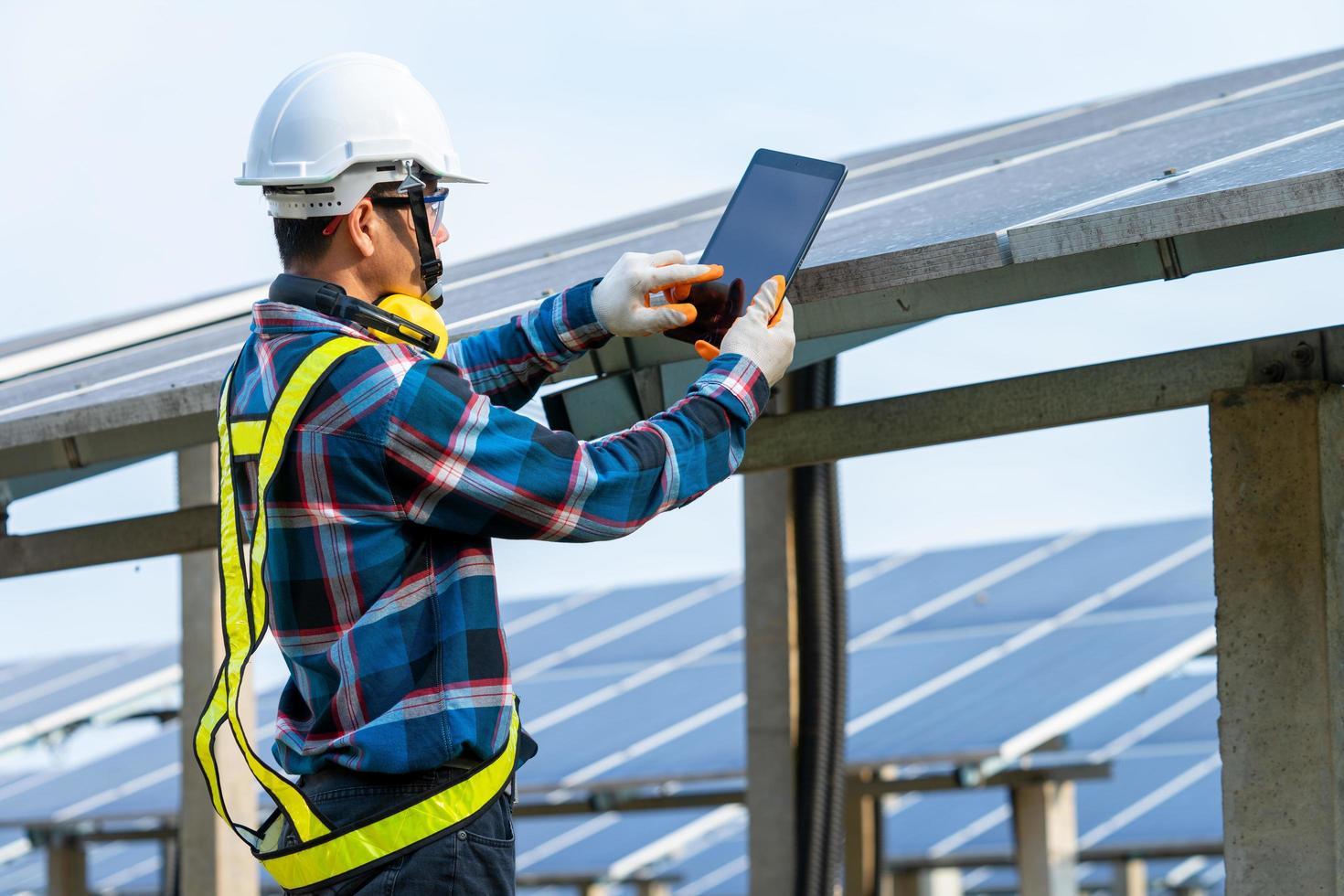 man bär säkerhetsutrustning bredvid solpaneler foto