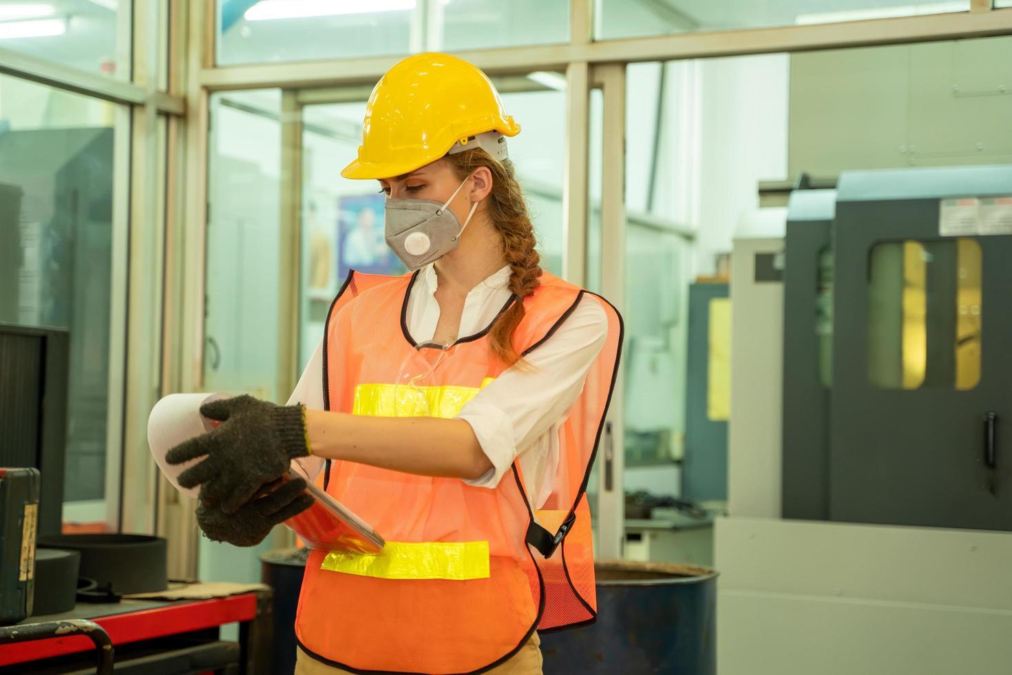 kvinna som bär mask med urklipp i fabriken foto