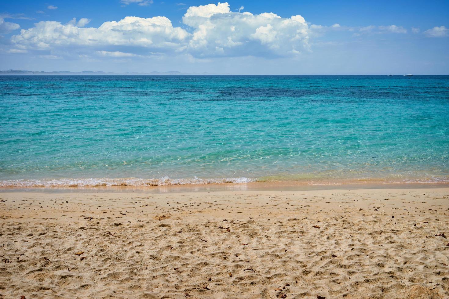 strand och vatten med molnig blå himmel foto