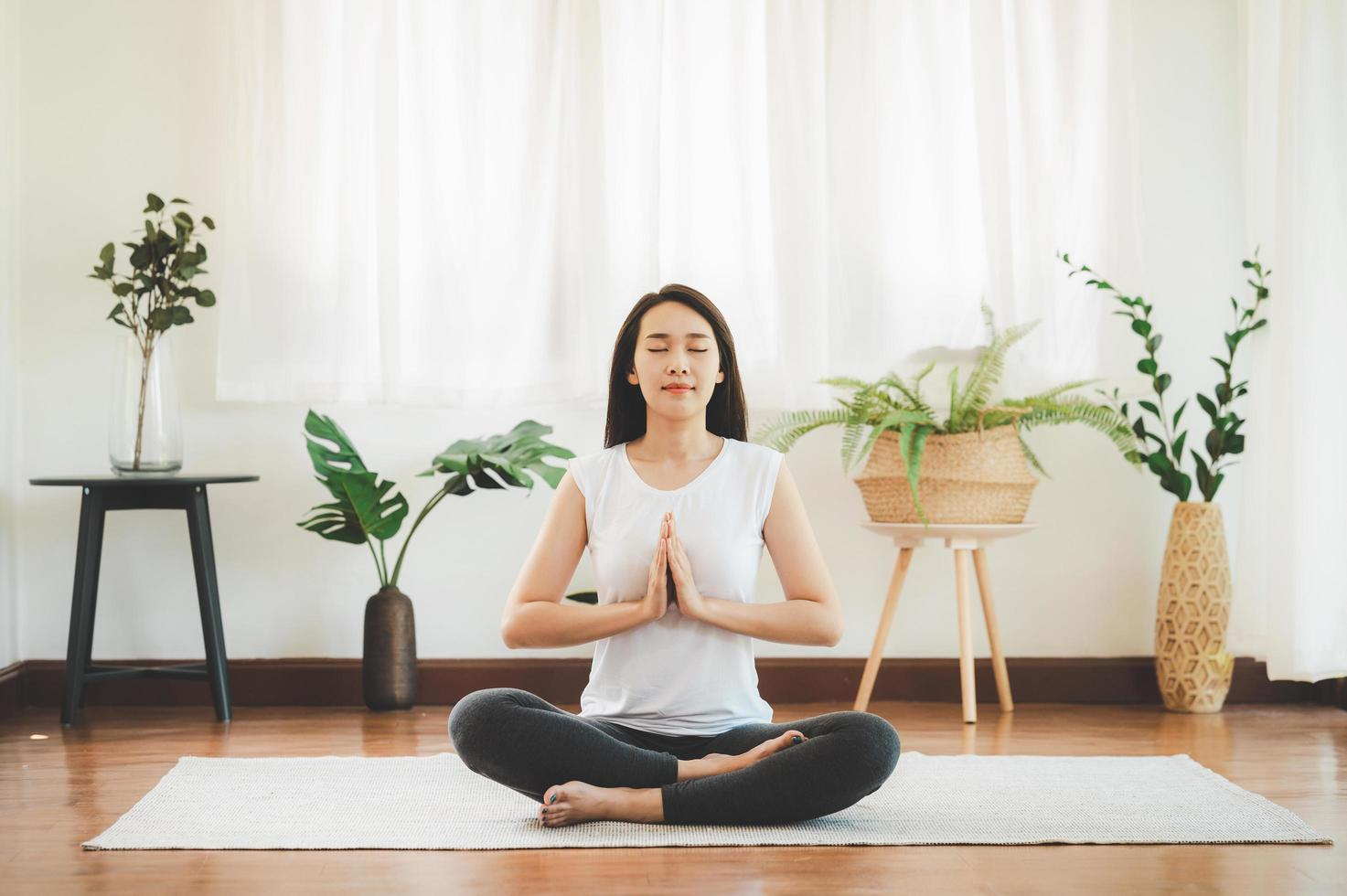 asiatisk kvinna som gör yogameditation hemma foto