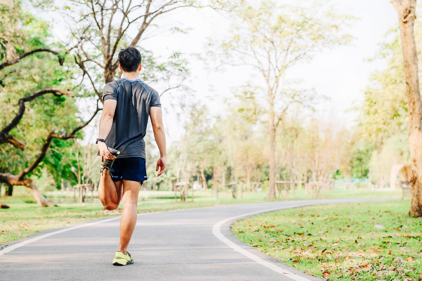 manlig löpare som gör stretchövning foto