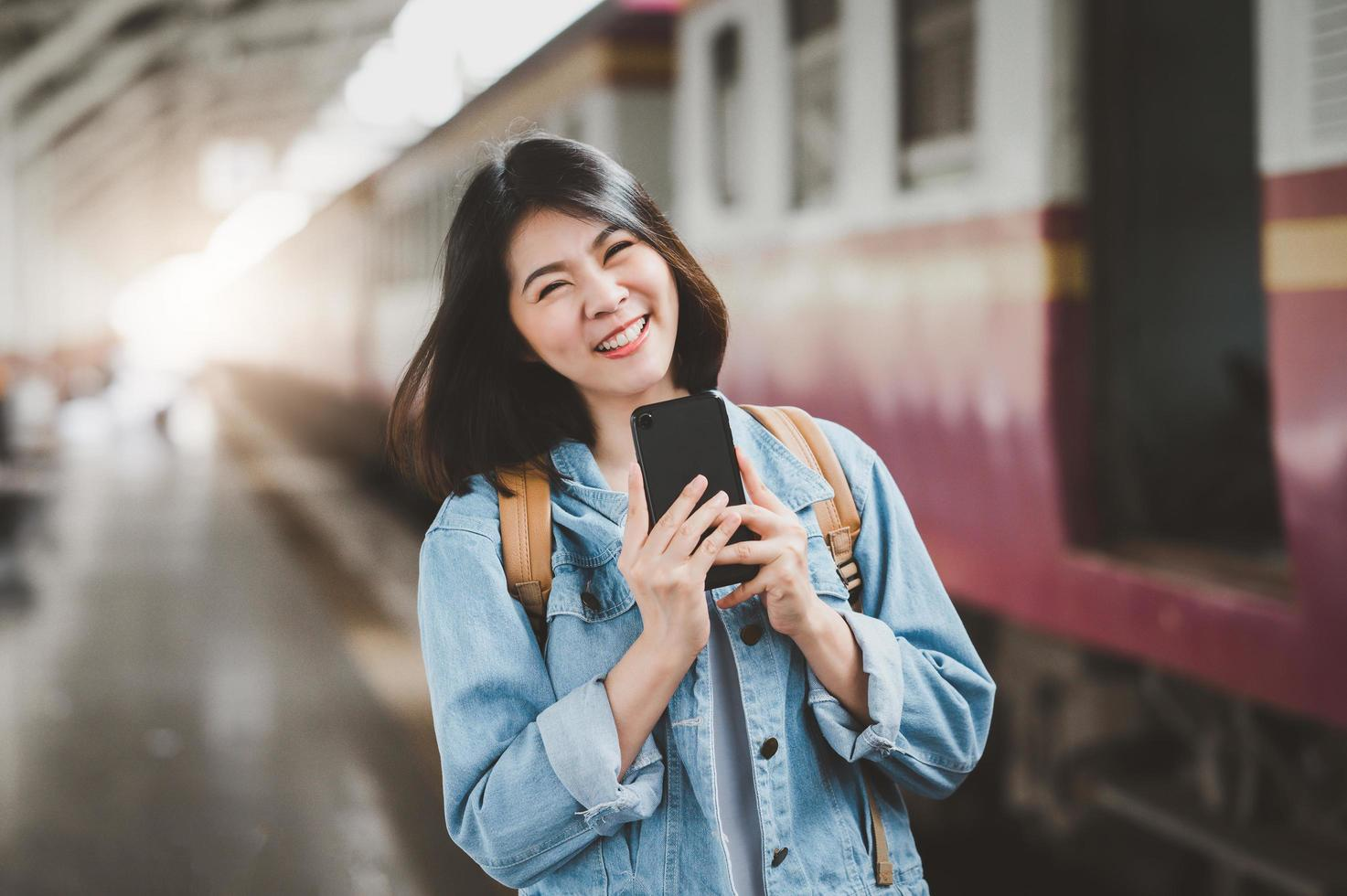 glad asiatisk kvinna på tågstationen foto