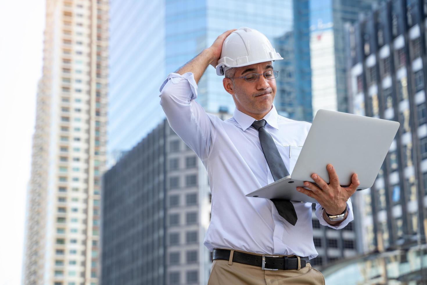 affärsman i hård hatt med bärbar dator foto