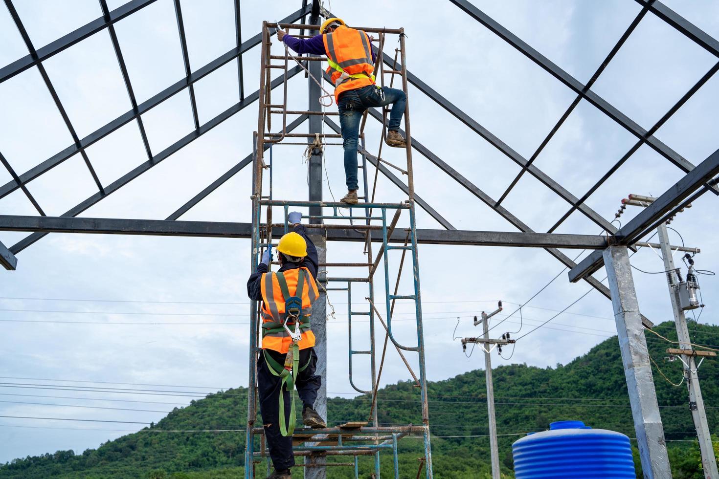 byggnadsarbetare som bär säkerhetssele på byggnadsställningar foto