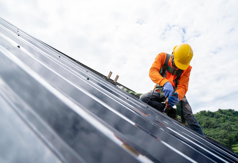 byggnadsarbetare som bär säkerhetsutrustning på taket foto