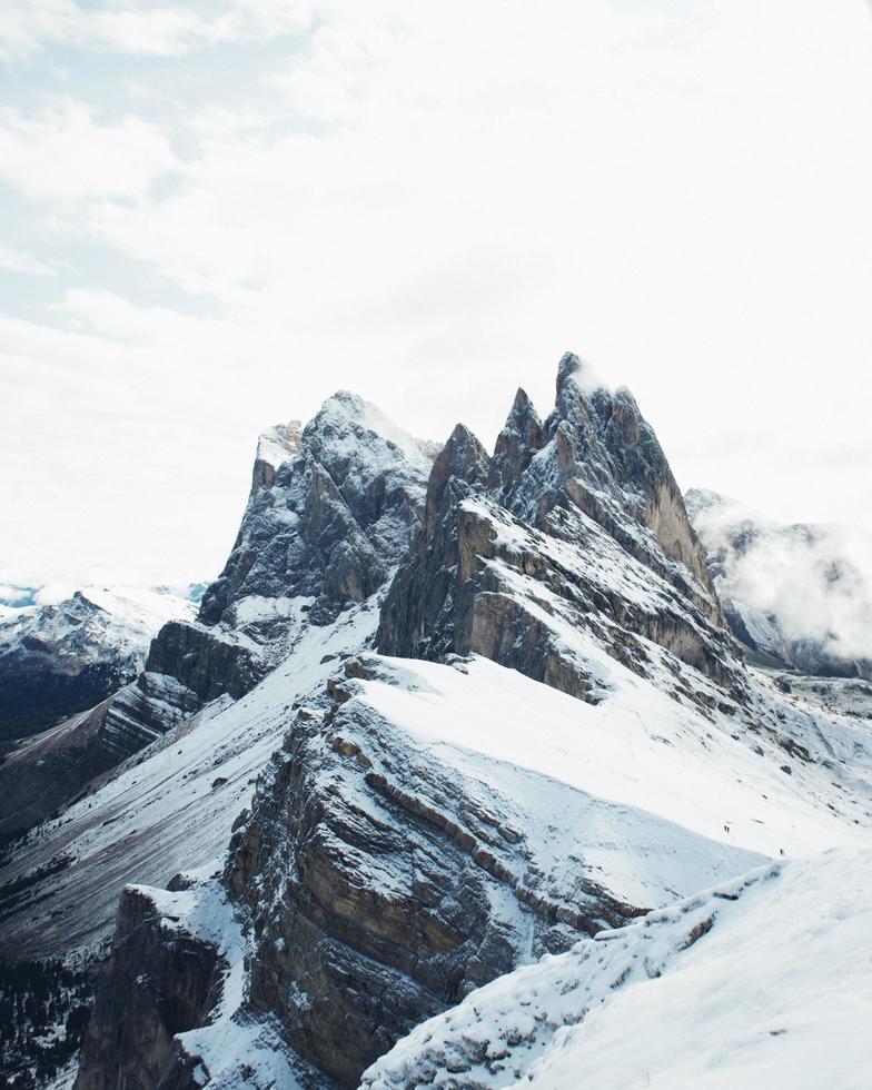 snöklädda berg under molnig blå himmel foto
