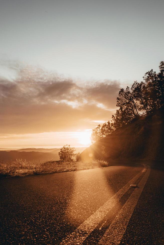 slingrande väg genom kullarna vid soluppgången foto