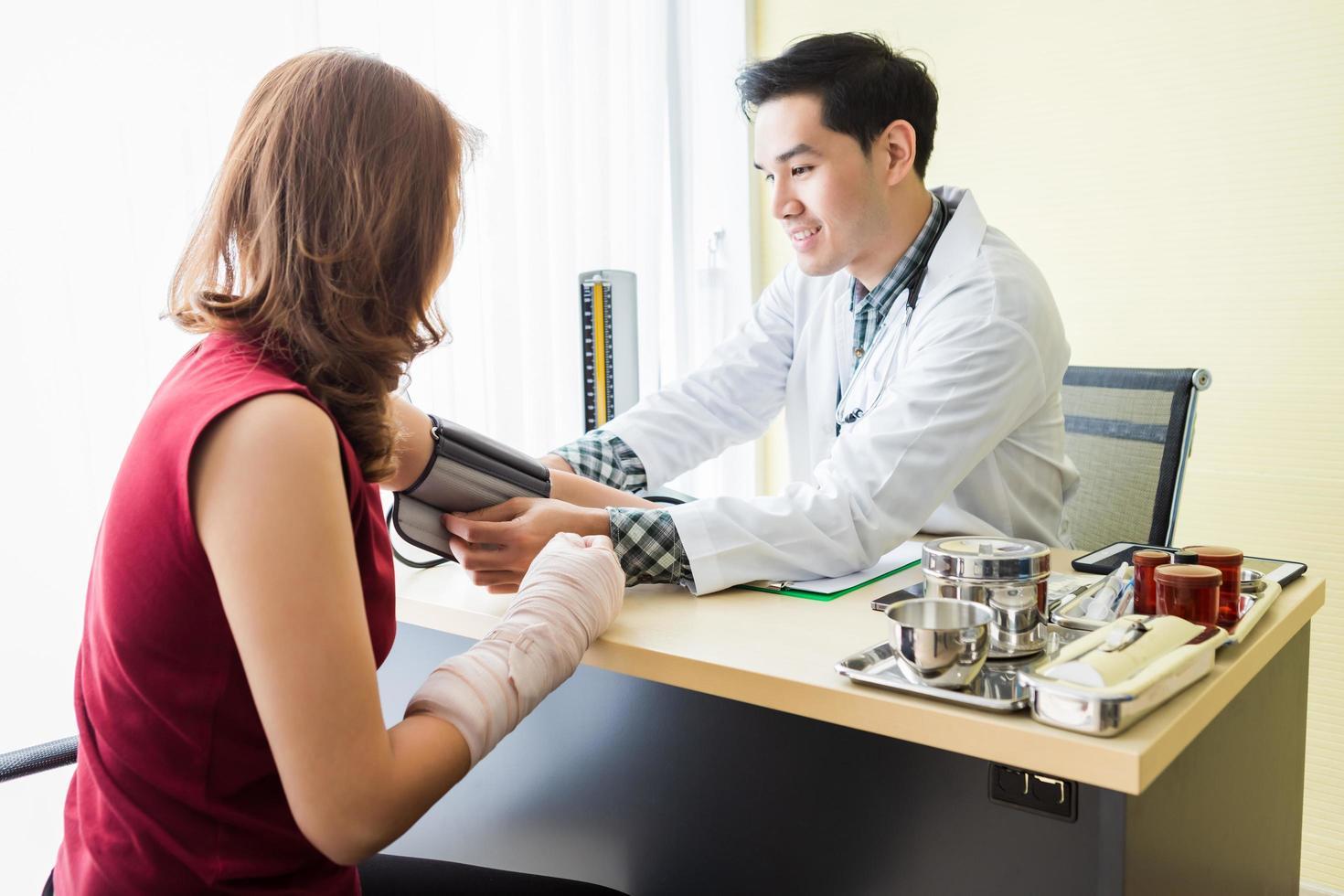 asiatisk ung manlig läkare med kvinnlig patient foto