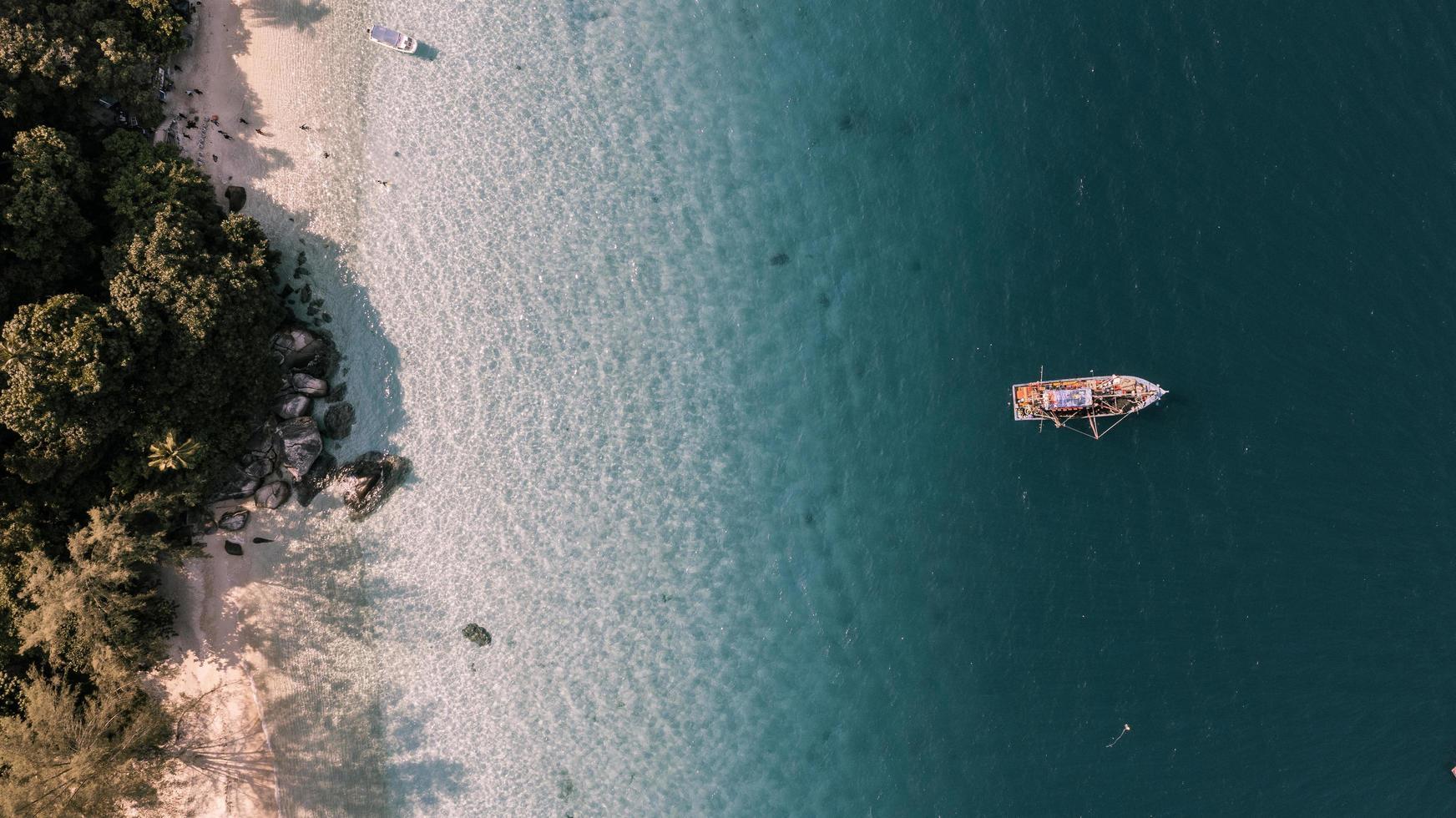 Flygfoto över båt i havet nära en strand foto