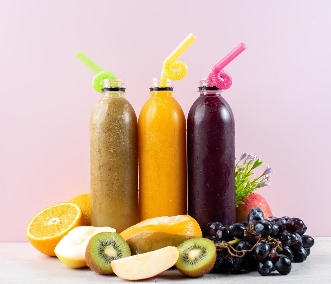 flaskor juice med frukt foto