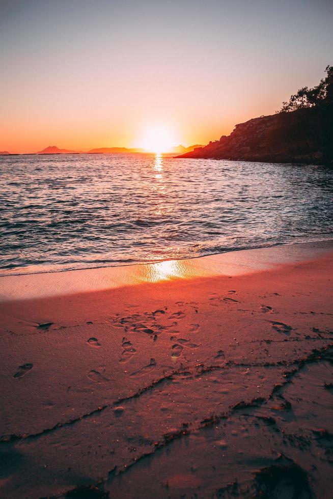 färgglad solnedgång över vatten och strand foto