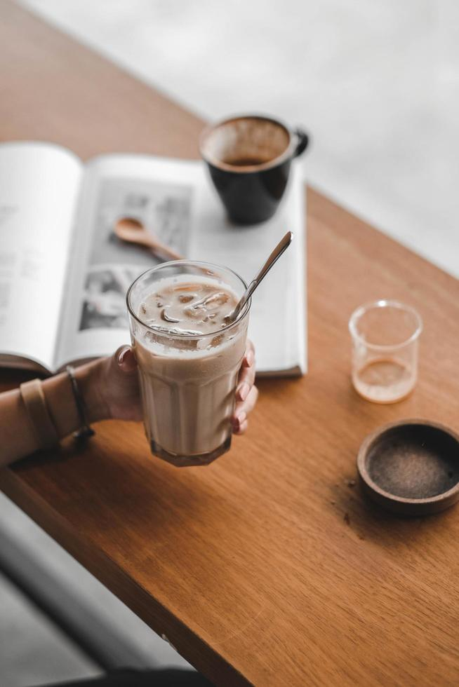person som håller isade latte foto