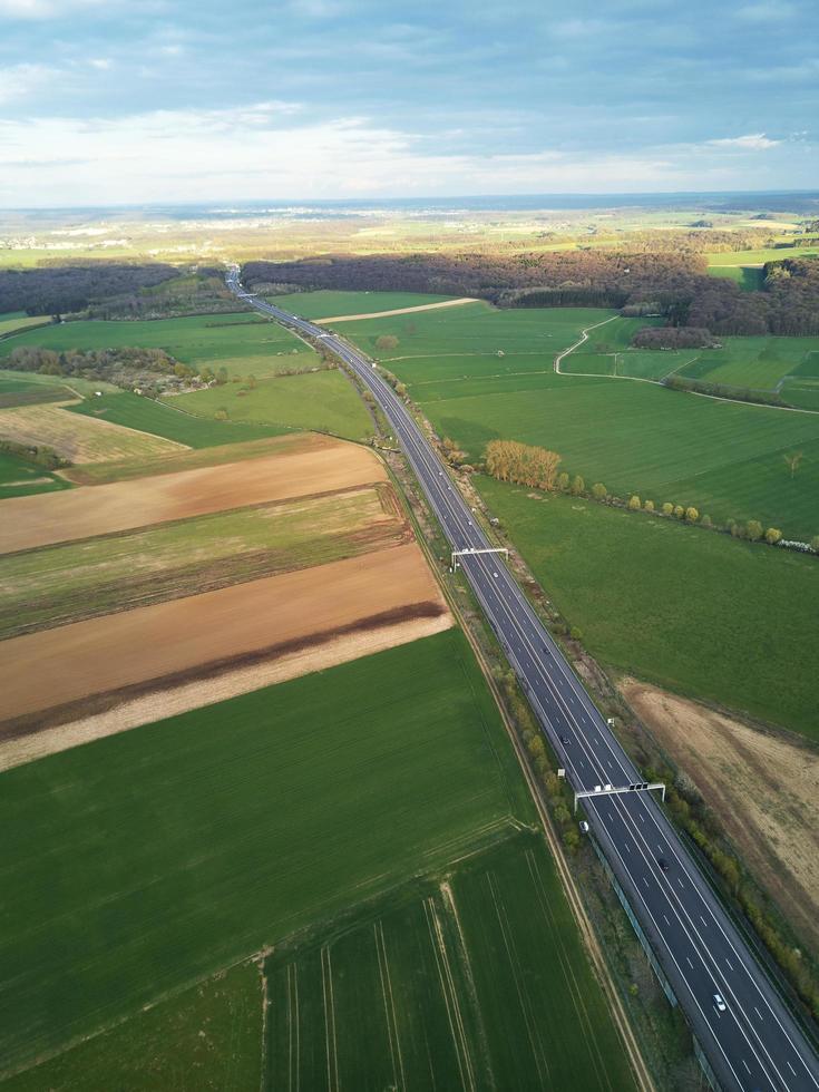 Flygfoto över en motorväg mellan fält med grönt gräs foto