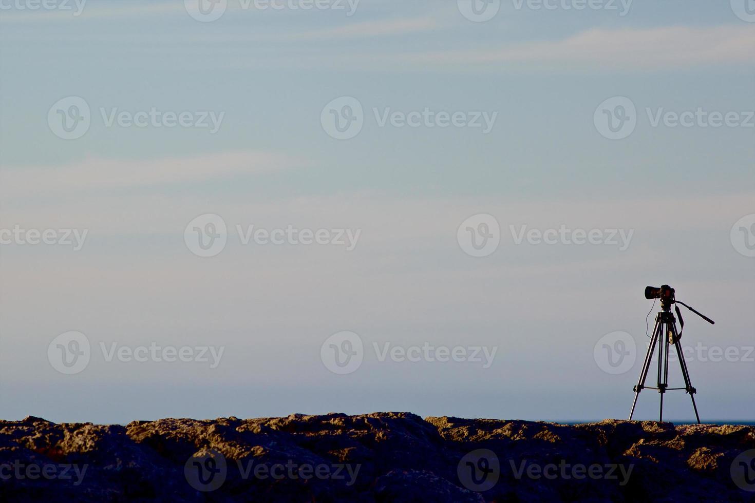 digital kamera på ett stativ med solnedgångshimmel foto
