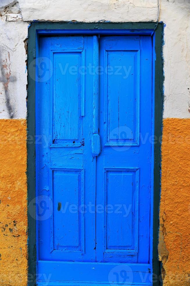 blå dörr på gul vägg foto