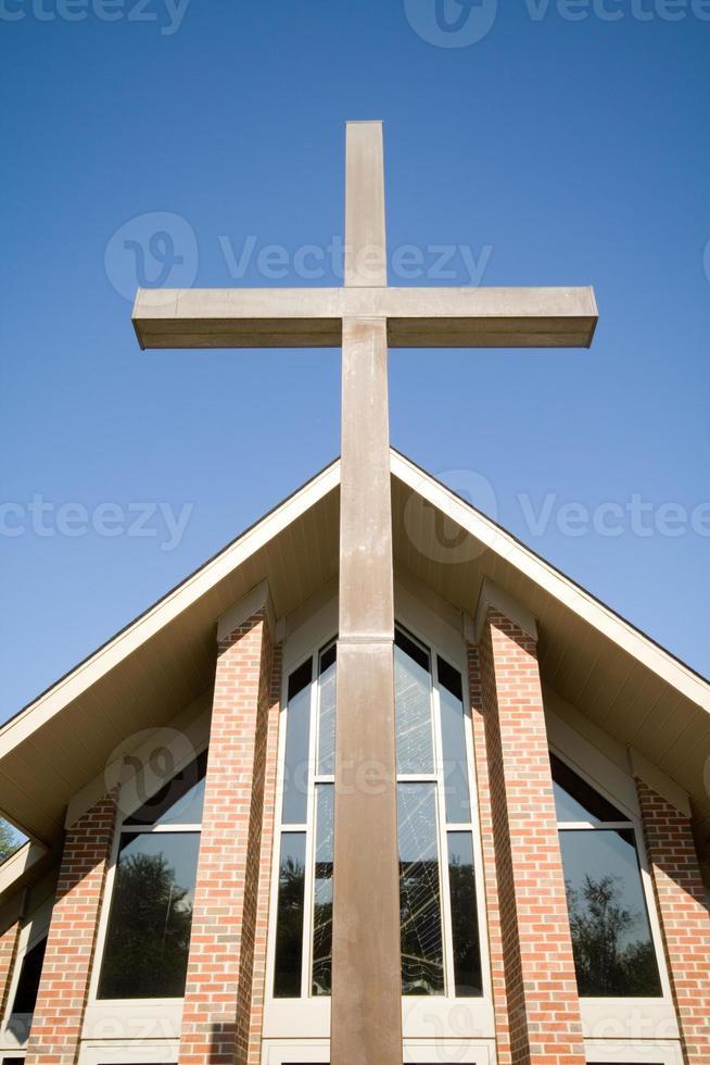 stort kors framför modern kyrktakblå himmel foto