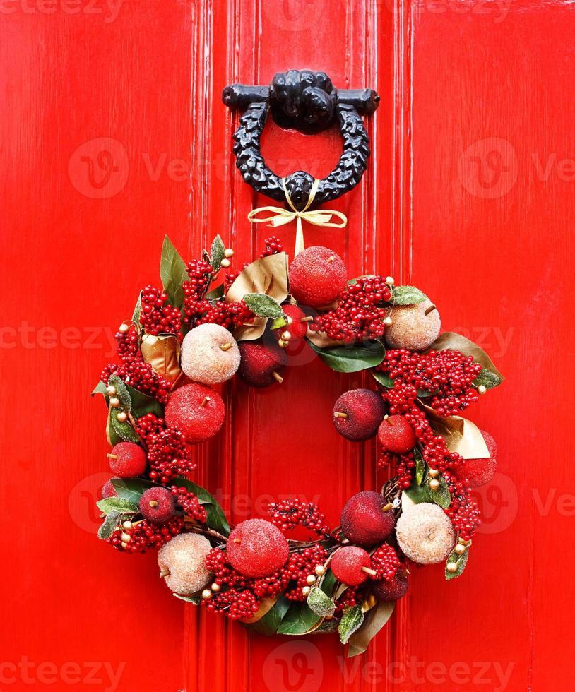 festlig julkrans som hänger på den röda dörren foto