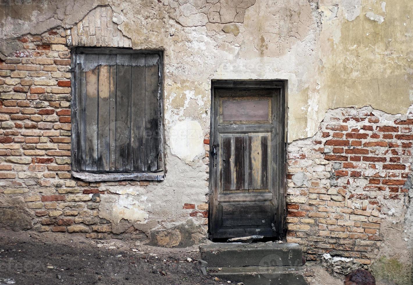 gamla fönster och dörr med sprucken vägg foto