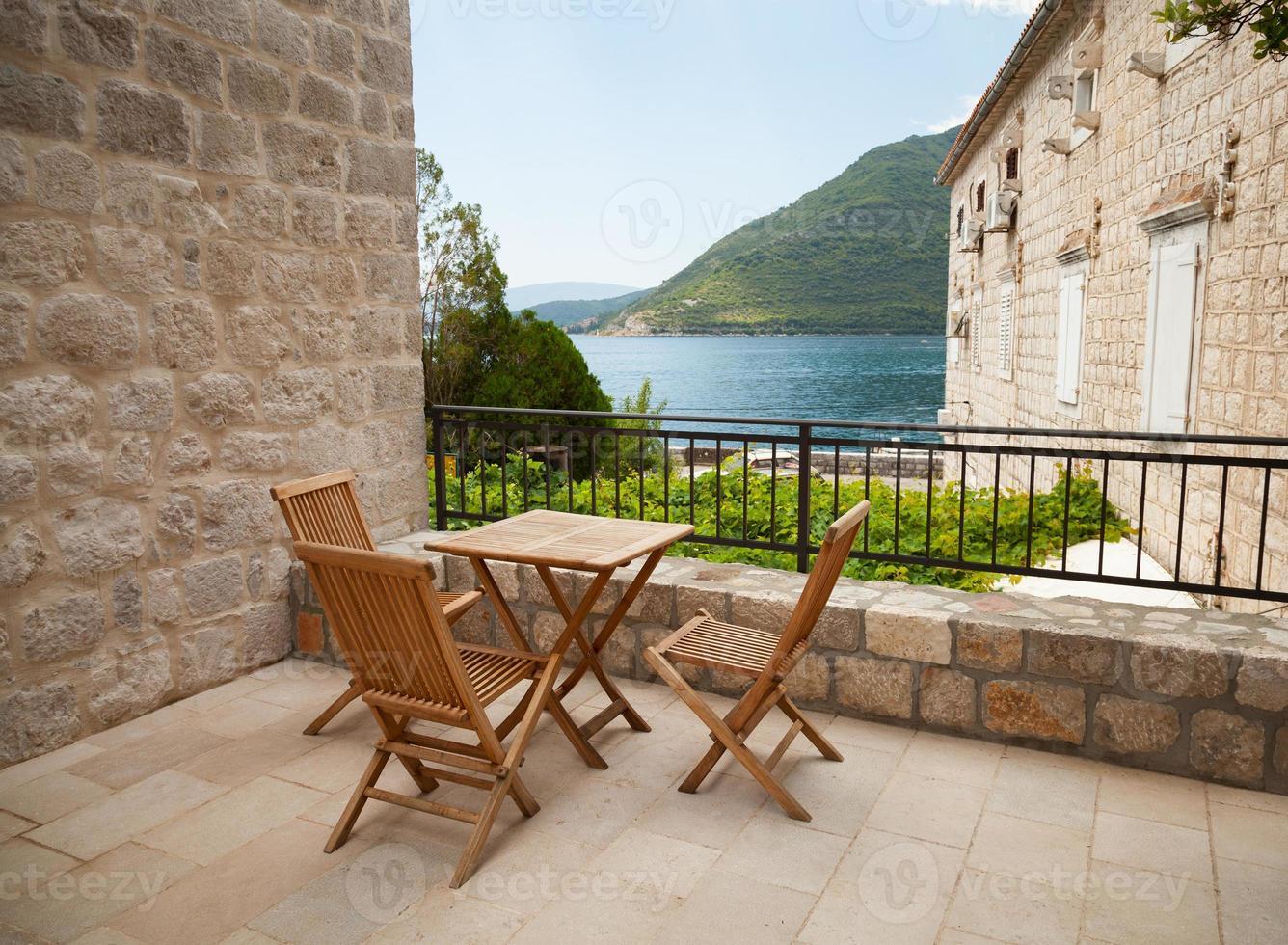 trästolar och bord på öppen terrass vid havet foto