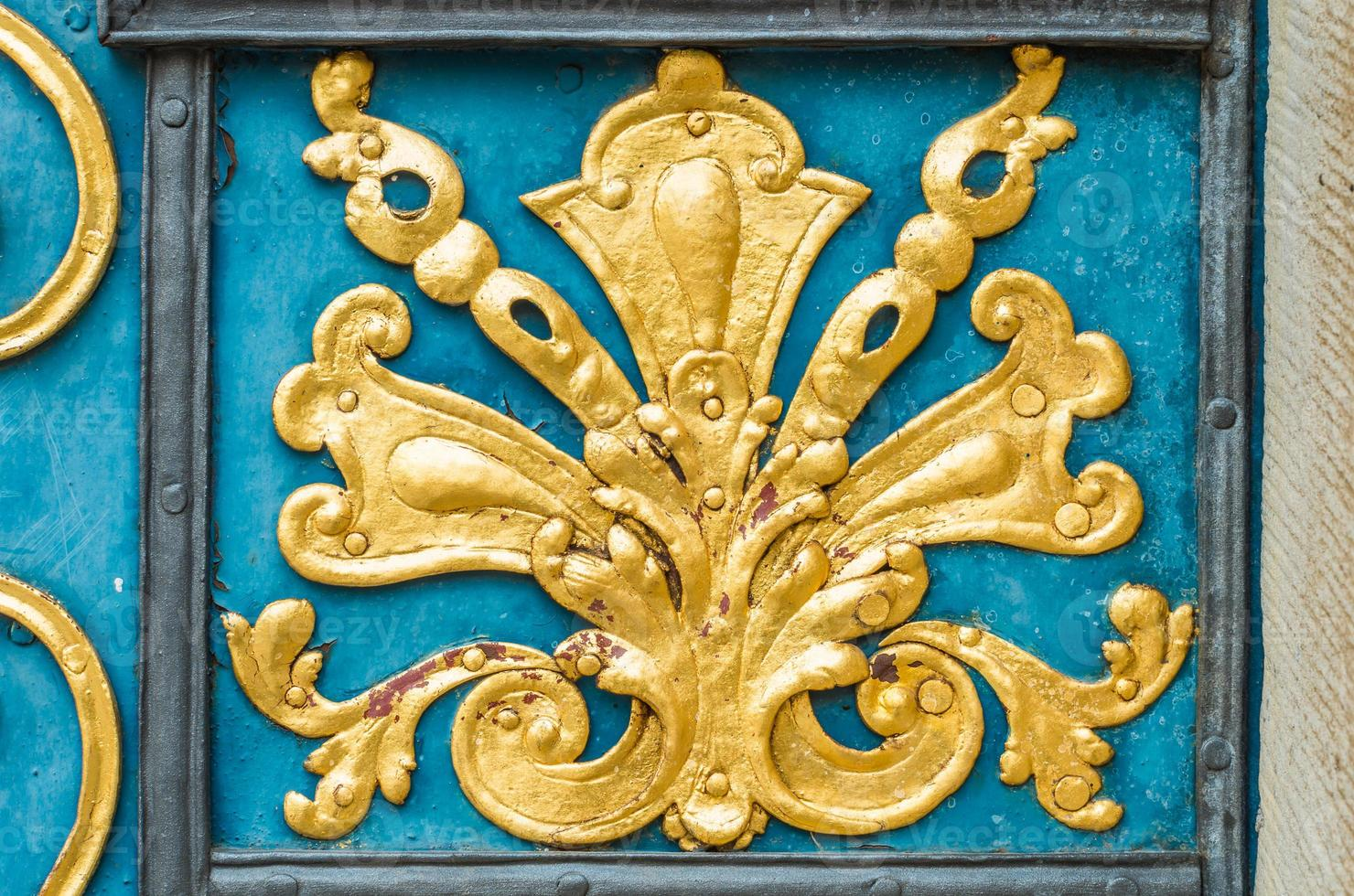 detalj av blå dörr dekorerad med gyllene prydnad foto