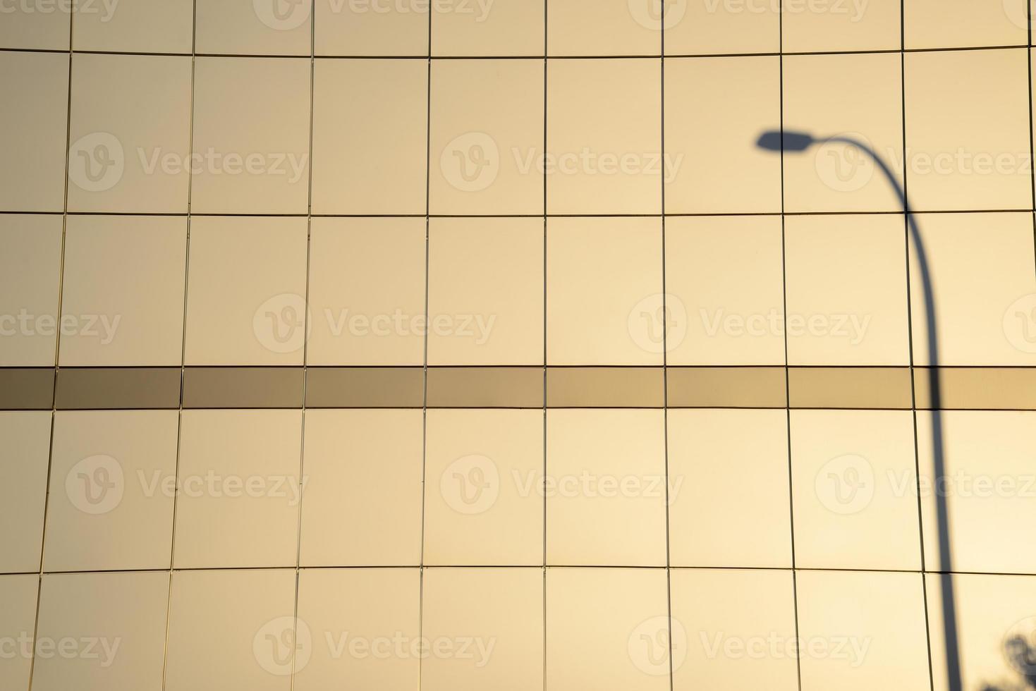 fasad på en byggnad i skuggan av en lyktstolpe. foto