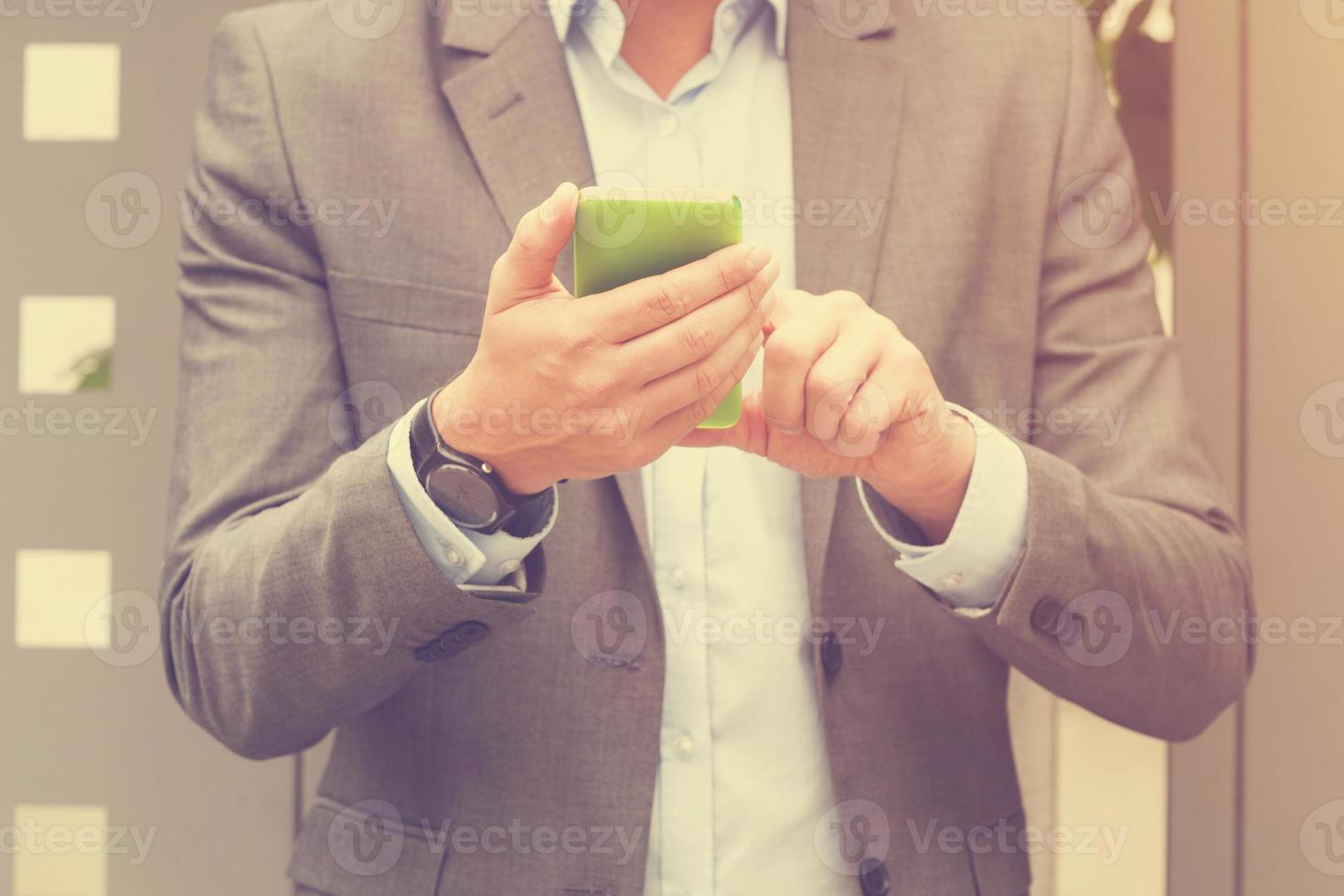 elegant man som använder mobiltelefon utomhus. foto