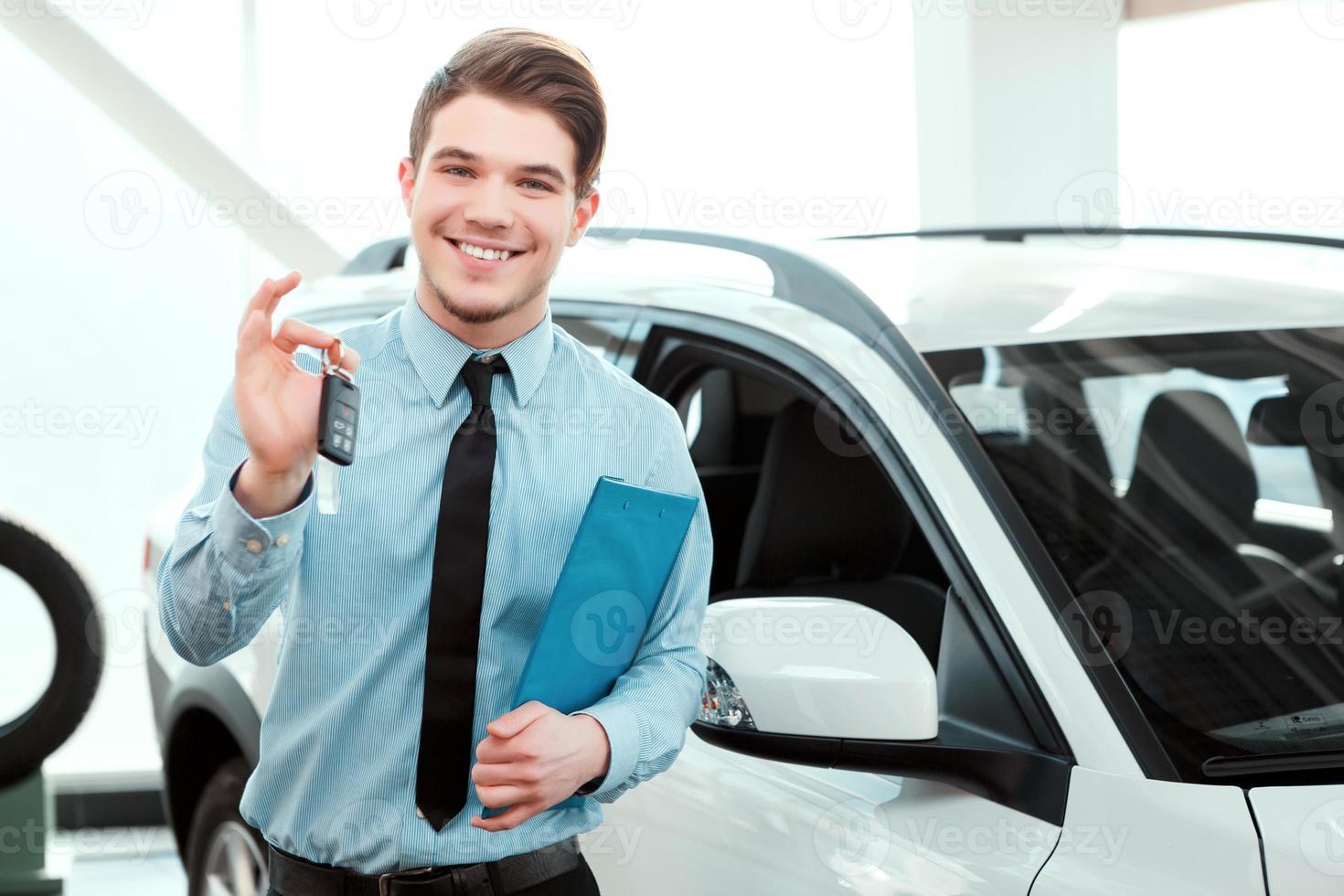 leende ung man som håller upp bilnycklar bredvid en ny bil foto