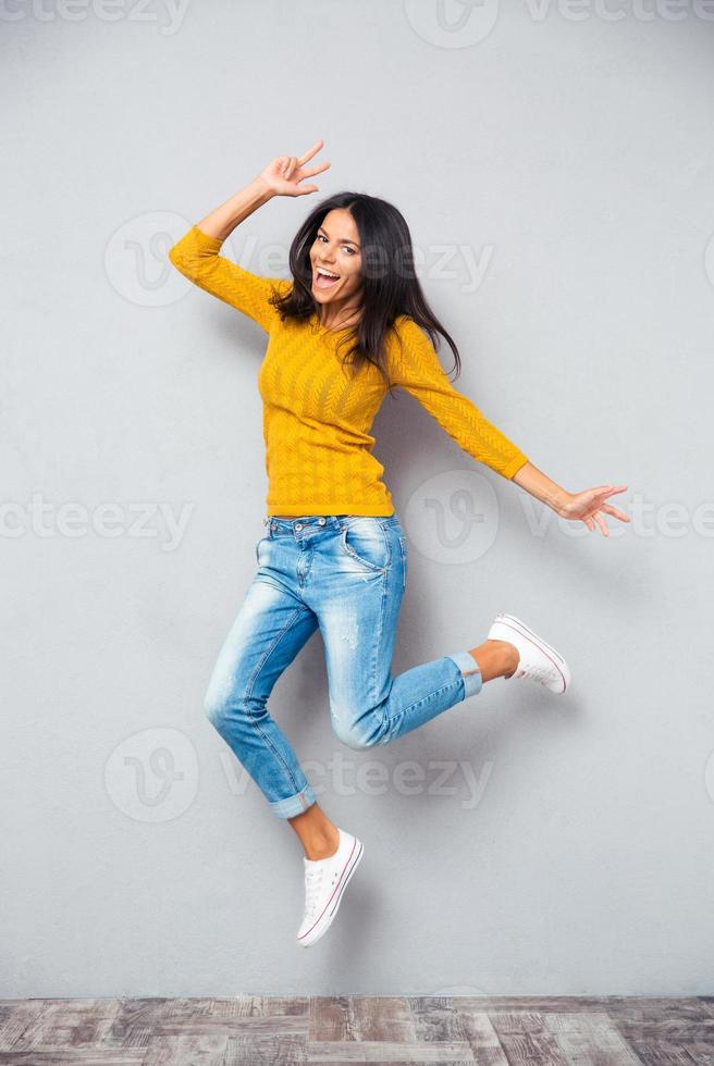 full längd porträtt av en rolig kvinna hoppa foto