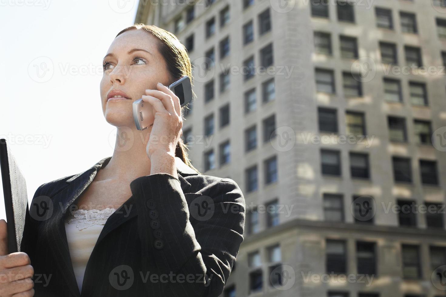 affärskvinna som använder mobiltelefon mot byggnad foto