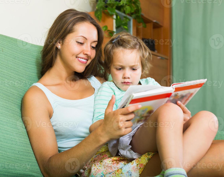mor och dotter läser bok foto