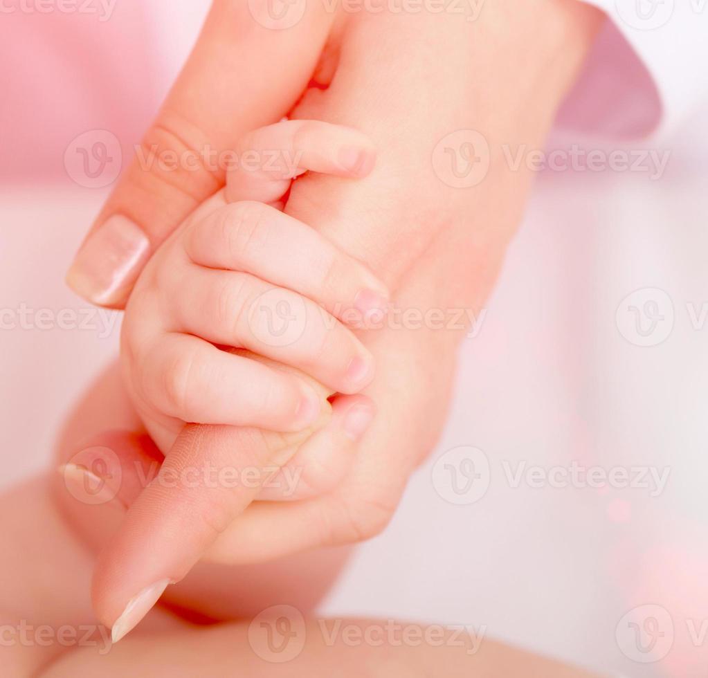 barnets hand med mammas finger foto