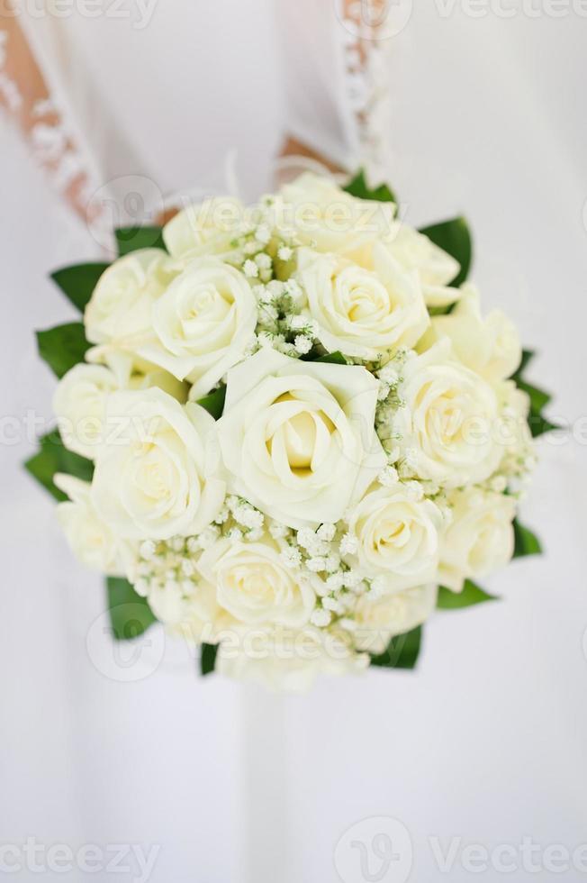bröllop bukett med många vita rosor i händerna på bruden foto