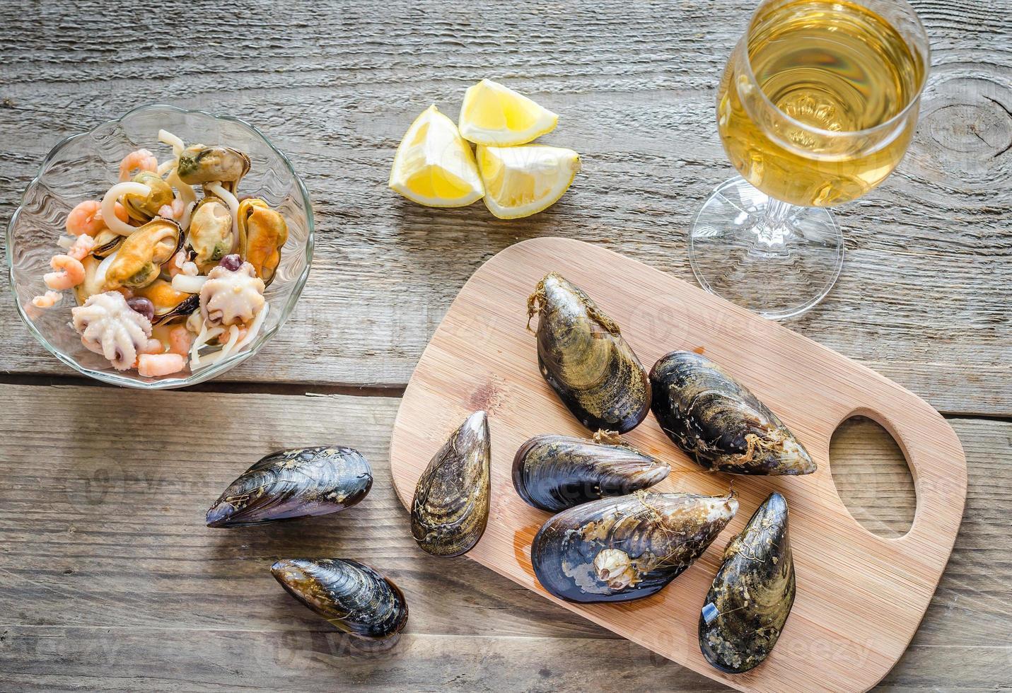 musslor med ett glas vin på träbordet foto