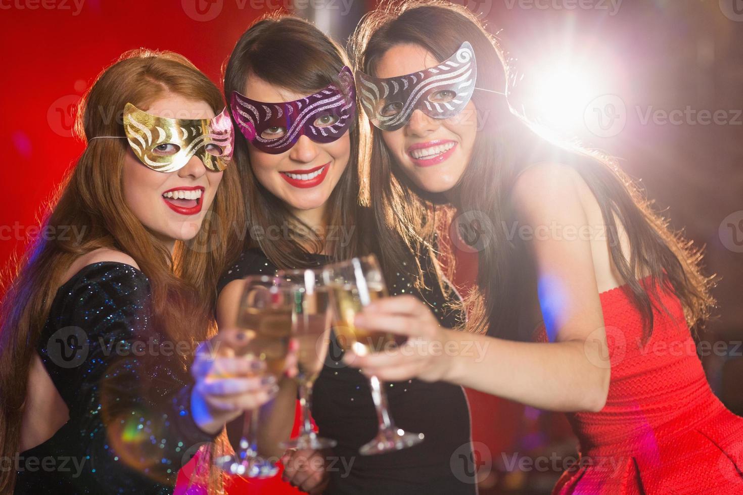 vänner i maskeradmasker som rostar med champagne foto