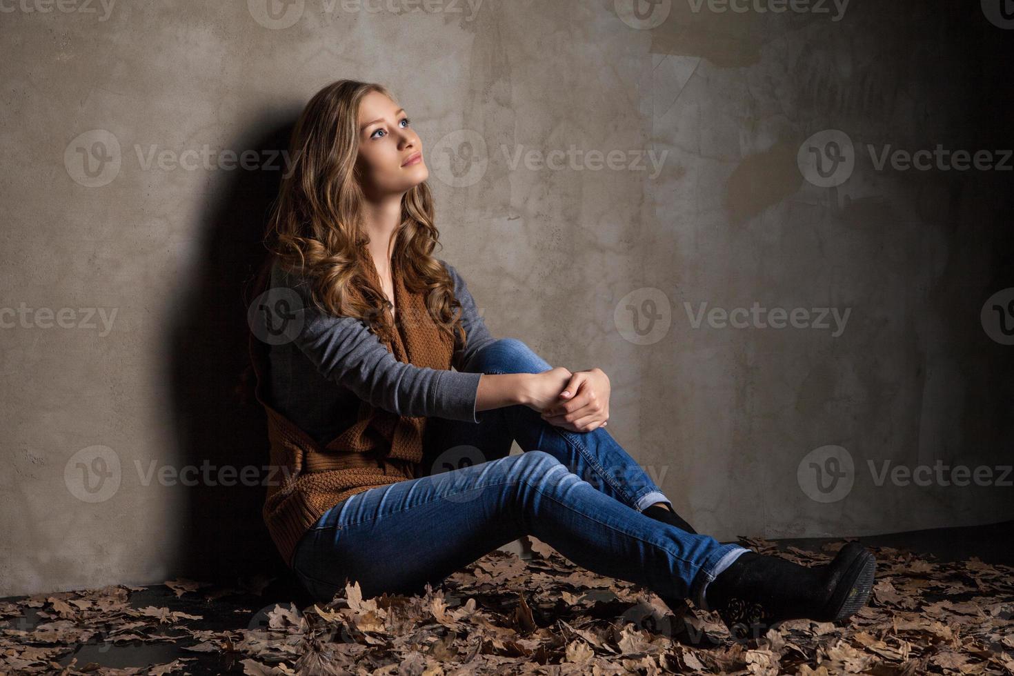 ung kvinna i jeans med höstlöv foto