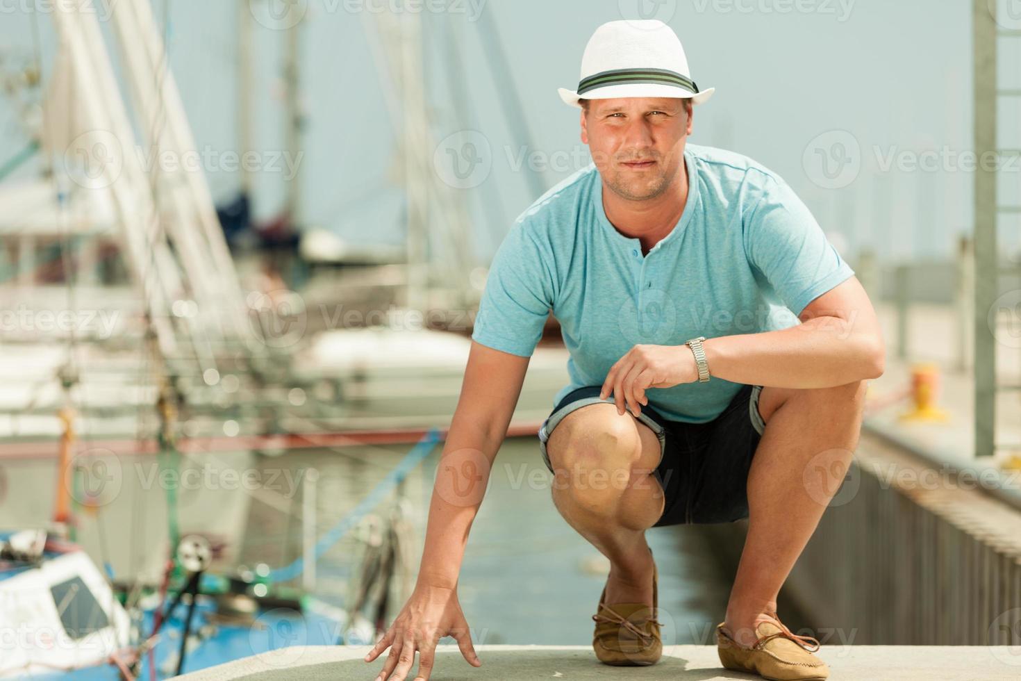 modestående av den stiliga mannen på piren mot yachter foto