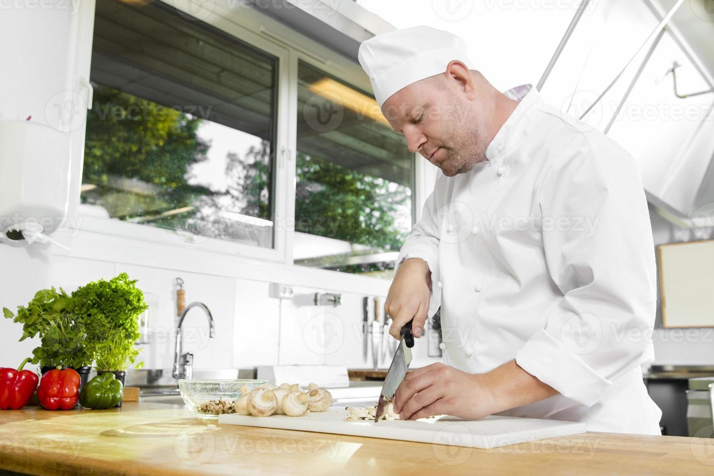 professionell kock som förbereder grönsaker i stort kök foto