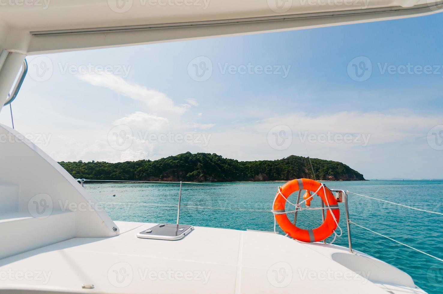 privat katamaranbåt som flyter nära ön. lyxig livsstil foto