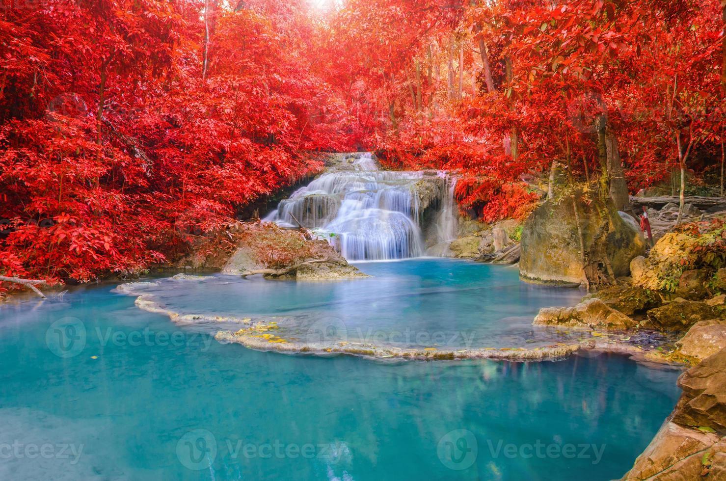 underbart vattenfall med regnbågar i djup skog vid nationella par foto