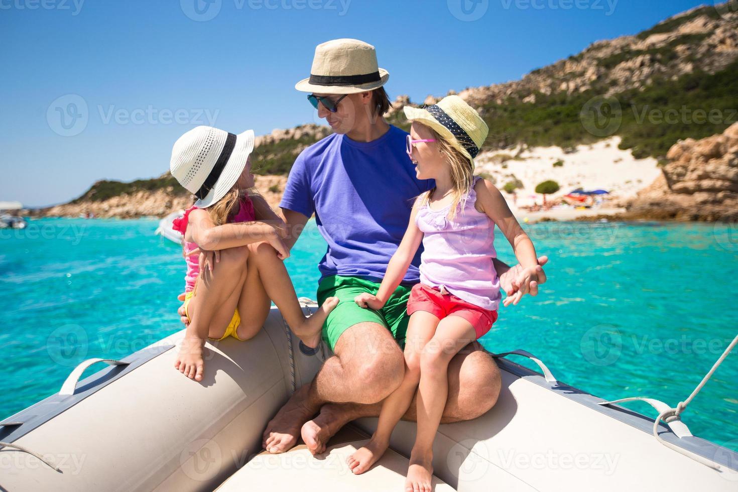 ung far med bedårande flickor som vilar på en stor båt foto