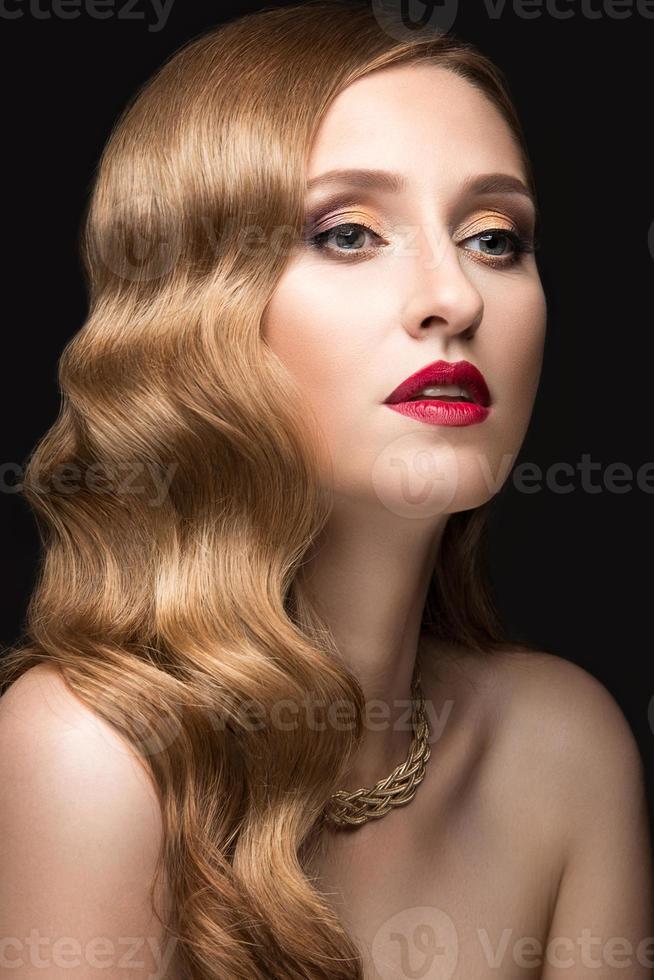 vacker kvinna med kvällsmink, röda läppar och lockar foto