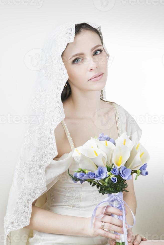 ung vacker brud med en bröllopsbukett foto