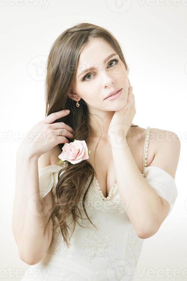 studio porträtt av ung vacker brud i en vit klänning foto
