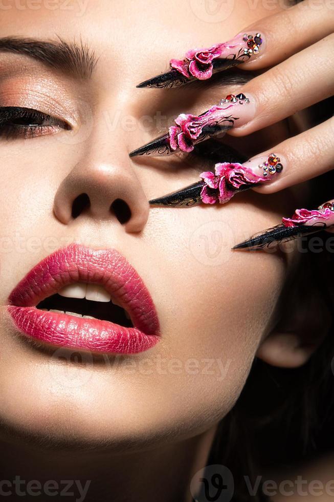 vacker flicka med långa naglar och sensuella läppar. skönhet ansikte foto