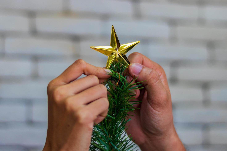 folk sätter stjärna på julgran foto