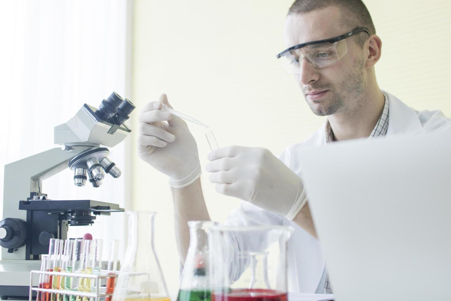 forskare som håller en dropper och ett provrör. foto