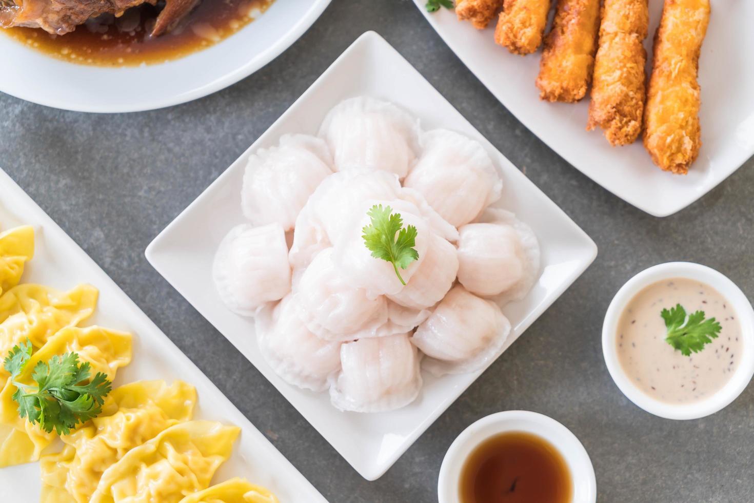 ångade räkor, dumplings omgiven av andra plattor foto