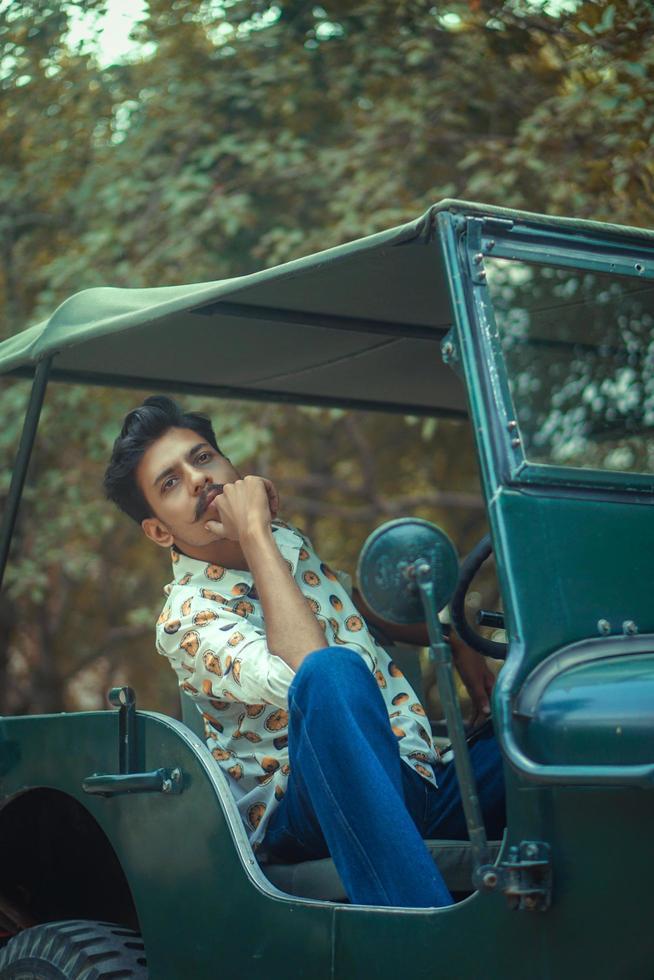 ung man sitter i en jeep foto